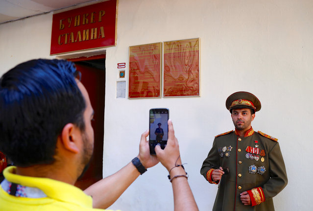 A tourist, visiting Russia during the Soccer World Cup, poses for a photograph dressed in a Russian military costume outside the entrance to Stalin's Bunker in Samara, Russia, on Tuesday, June 26, 2018. (Photo by David Gray/Reuters)