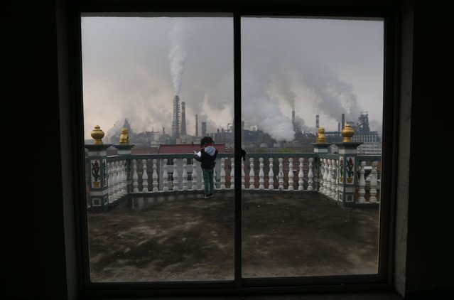 A girl reads a book on her balcony as smoke rises from chimneys of a steel plant, on a hazy day in Quzhou, Zhejiang province in this April 3, 2014 file photo. China's manufacturing growth stalled for the second straight month in January and companies had to cut prices at a faster clip to win new business, adding to worries about growing deflationary pressures in the economy, a private survey showed. (Photo by Reuters/Stringer)