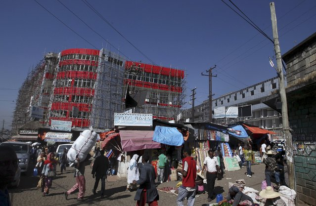 A new shopping centre under construction is seen behind old buildings and market stalls at the Mercato market in Addis Ababa November 18, 2015. (Photo by Tiksa Negeri/Reuters)