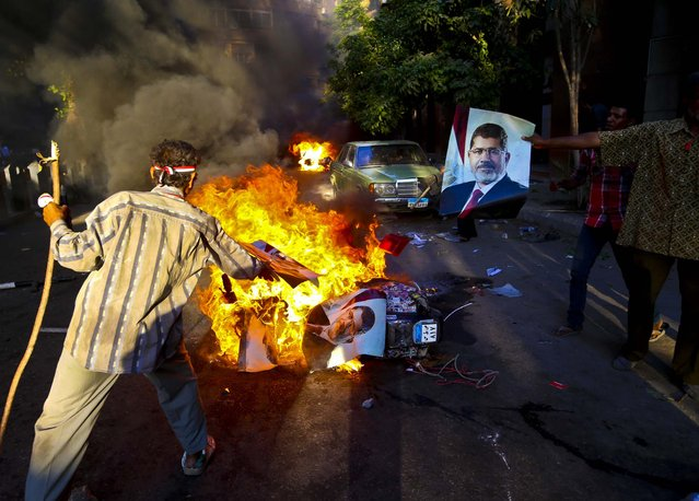 Opponents of ousted President Mohammed Morsi burn posters bearing his picture during clashes against Morsi supporters, in Cairo, Egypt, on July 23, 2013. (Photo by Hussein Malla/Associated Press)