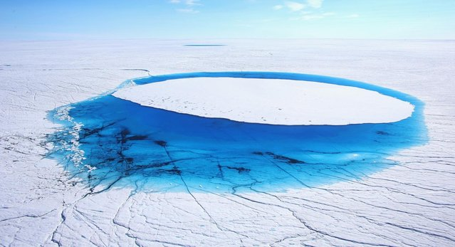Water is seen on part of the glacial ice sheet that covers about 80 percent of the country is seen on July 17, 2013 on the Glacial Ice Sheet, Greenland. (Photo by Joe Raedle/Getty Images via The Atlantic)
