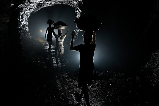 Bojharis carry coal chiselled out by coal cutters in an illegal underground coal mine in Eastern India. Average loads carried by these bojharis was around about 40 kilograms at a time. In this mine the miners had sought the input of a mining enginner to choose the placement of pillars within the mine and so minimise the risk of collapses. Eastern India, 2013. (Photo by Hugh Brown/South West News Service)