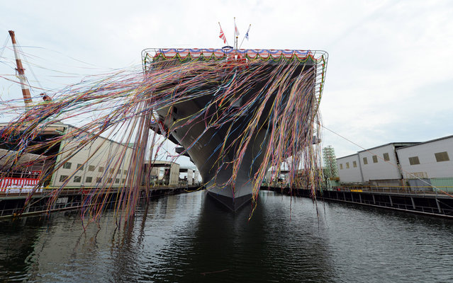 Japan's newest warship, the DDH183 Izumo, is pictured during a launch ceremony in Yokohama on August 6, 2013. The 248-metre-long and 19,500-tonne helicopter destroyer is the biggest warship since World War II in a move likely to jangle nerves among neighbours China and South Korea, as Tokyo mulls an overhaul of its pacifist constitution. (Photo by Toshifumi Kitamura/AFP Photo)
