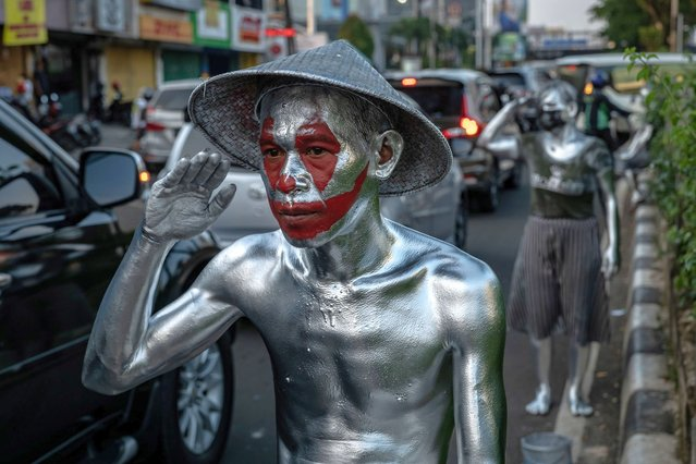 """Junaidi (40), wearing silver paint begs for money on the street, was an employee at a company, but due to the pandemic he was laid off and become a """"silver men"""" for a month on March 11, 2021 in Depok, Indonesia. """"Silver Men"""",  called """"Manusia Silver"""" in Indonesian language, are an economically underprivileged group of people who have turned to a special form of begging to make ends meet. Using a mixture of screen-printing powder and cooking oil to form a highly toxic improvised metallic paint, they coat their bodies for dramatic effect and transform themselves into living statues. Manusia Silver can earn about 50,000 Indonesian rupiah to 100.000 Indonesian rupiah ($3.50 to $7) per day. Indonesia's poor account for 26.42 million of a population of over 270 million, as the coronavirus pandemic disrupted business activity in Indonesia, 2.67 million people have lost their jobs, according to Statistics Indonesia (BPS). (Photo by Ulet Ifansasti/Getty Images)"""