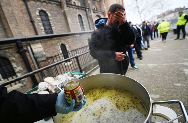Homeless people line up at a soup kitchen in north London, Britain, 02 March 2021. Measures put in place to help homeless people by the British Government, including a ban on evictions from social and privately rented accommodation have made a huge difference in the cases of new homelessness in the last year. The eviction ban however, which is set to end in April is likely to push many people back on to the streets. (Photo by Andy Rain/EPA/EFE)