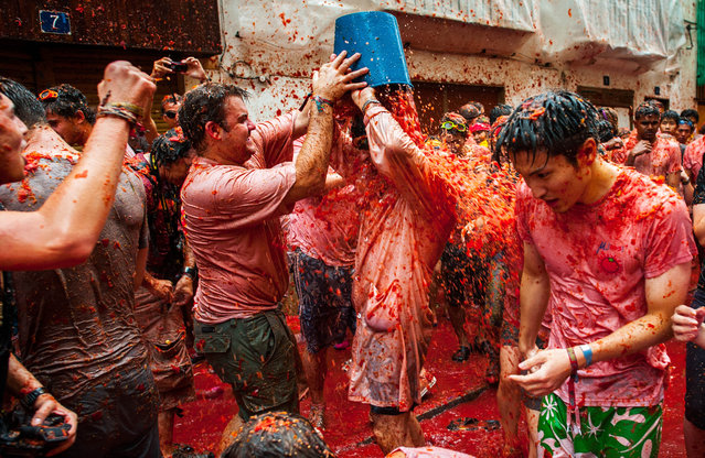 Revellers celebrate covered by tomato pulp while participating the annual Tomatina festival on August 28, 2013 in Bunol, Spain. An estimated 20,000 people threw 130 tons of ripe tomatoes in the world's biggest tomato fight held annually in this Spanish Mediterranean town.  (Photo by David Ramos/Getty Images)