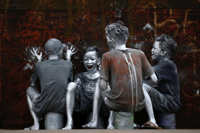 """Youths, who covered themselves from head to toe in silver paint to become """"manusia silver"""" (silvermen), as part of their act to make a living, laugh as they ride on the back of a truck in Jakarta, Indonesia, March 31, 2021. (Photo by Willy Kurniawan/Reuters)"""
