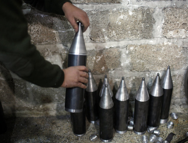 """A """"Free Syrian Army"""" fighter makes homemade missiles at a workshop in north Aleppo December 29, 2012. (Photo by Ahmed Jadallah/Reuters)"""