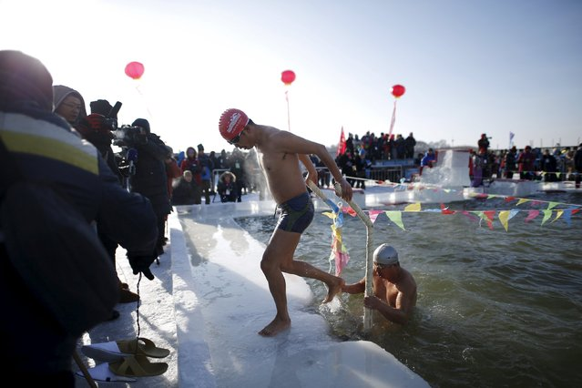 Swimmers climb out a pool carved from thick ice covering the Songhua River during the Harbin Ice Swimming Competition in the northern city of Harbin, Heilongjiang province, January 5, 2016. (Photo by Aly Song/Reuters)