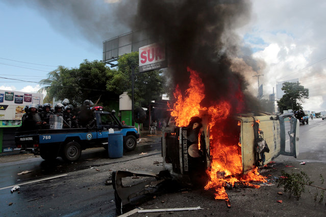 Riot police officers travel past a burning police car during a protest against Nicaraguan President Daniel Ortega's government in Managua, Nicaragua on September 2, 2018. (Photo by Oswaldo Rivas/Reuters)
