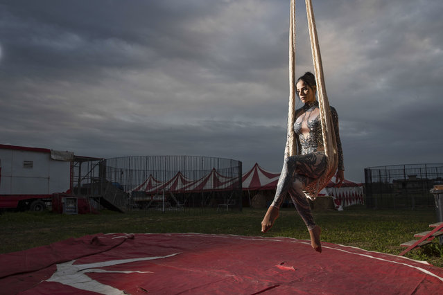 """Otilia Maria Martinez Dos Santos, an artist of Portuguese origin, poses for a portrait at the Rony Roller circus, parked in the outskirts of Rome, Saturday, April 18, 2020. Photographer Alessandra Tarantino said she came up with the idea to shoot circus workers after growing frustrated and bored with the postcard-like shots of an empty Rome during lockdown. The shot was taken between poses, with the swing seemingly attached to the sky. """"Her empty gaze, lost in the void, deeply affected me. It's hard to dance without the music"""", Tarantino said. (Photo by Alessandra Tarantino/AP Photo)"""
