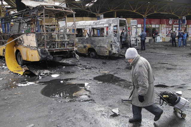 A local man walks past damaged buses at a bus station in Donetsk, Ukraine, February 11, 2015. (Photo by Alexander Ermochenko/EPA)