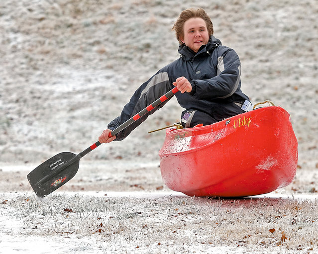 Cabot Anderson rides a kayak down an ice covered hill on the greenbelt in Blount County near the Blount County Library Tuesday, February 17, 2015 after heavy ice covered Blount County Monday closing schools and many businesses on Monday. (Photo by Tom Sherlin/AP Photo/The Daily Times)