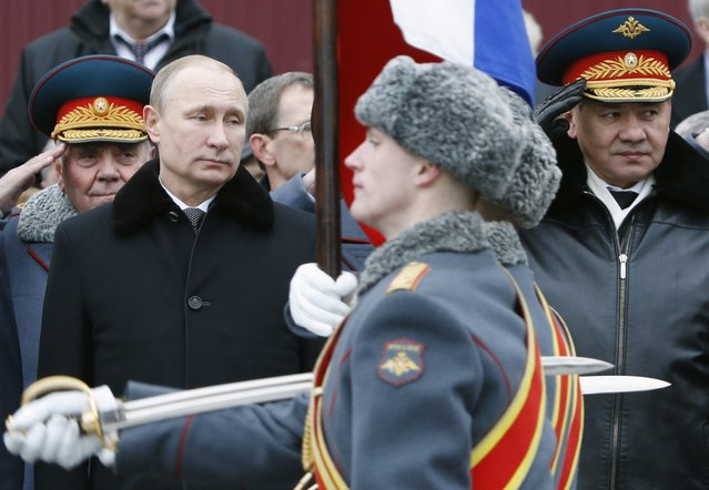 Russian President Vladimir Putin (L) and Defence Minister Sergei Shoigu (R, front) watch honor guards pass by as they attend a wreath laying ceremony to mark the Defender of the Fatherland Day at the Tomb of the Unknown Soldier by the Kremlin walls in central Moscow February 23, 2015. (Photo by Sergei Karpukhin/Reuters)