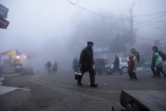 A vendor walks on a foggy cold winter day while offering Kahwa, a traditional green tea, in the hill-resort town of Murree, northeast of capital Islamabad, Pakistan, January 12, 2016. (Photo by Faisal Mahmood/Reuters)