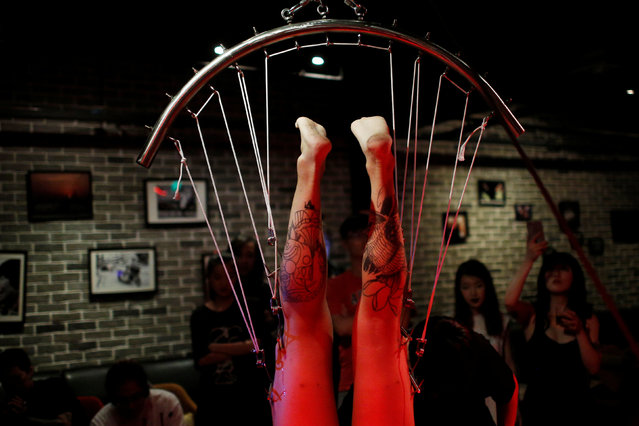 Angus Shen is suspended from hooks pierced through his skin by professional body artist Wei Yilaien at a bar in Shanghai, China on September 16, 2018. (Photo by Aly Song/Reuters)