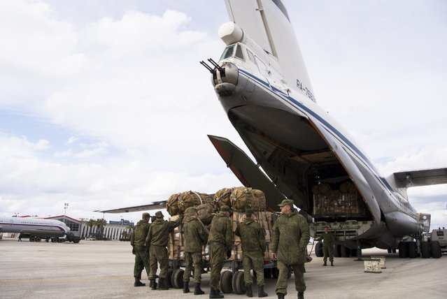 Russian air force personnel prepare to load humanitarian cargo on board a Syrian plane at Hemeimeem air base in Syria, Wednesday, January 20, 2016. (Photo by Vladimir Isachenkov/AP Photo)