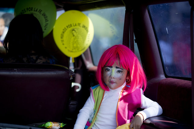 In this December 14, 2015, file photo, a young clown rides in the back of a car following a procession to the Basilica of Our Lady of Guadalupe in Mexico City. Hundreds belonging to various clown associations made their annual pilgrimage to the Basilica to pay their respects to the Virgin of Guadalupe, Mexico's patron saint. (Photo by Rebecca Blackwell/AP Photo)