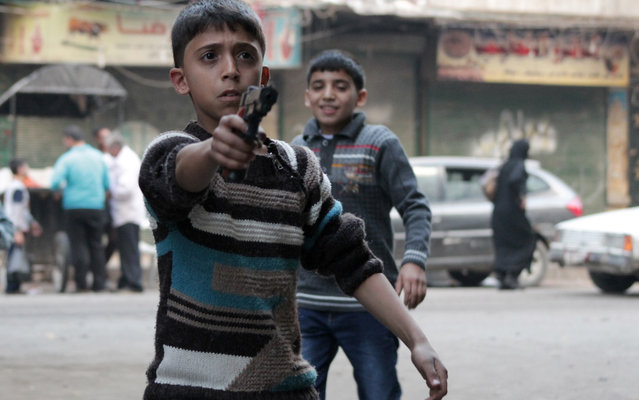 """A child plays with a toy gun in the Bustan al-Qasr neighbourhood of the northern Syrian city of Aleppo on October 15, 2013. The United States said there was an """"urgent"""" need to set a date for so-called Geneva 2 peace talks, despite a leading opposition group's rejection of the process. (Photo by Karam Al-Masri/AFP Photo)"""