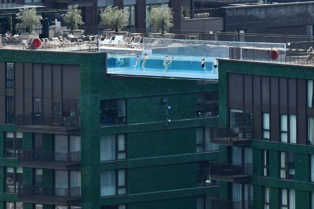 People swim in the Sky Pool – a transparent acrylic swimming pool bridge that is fixed between two apartment blocks – at Embassy Gardens in south-west London on June 3, 2021, as the city enjoys another sunny day. Much of Britain has enjoyed several days of fine weather with top temperatures reaching above 25 degrees Celsius. (Photo by Justin Tallis/AFP Photo)