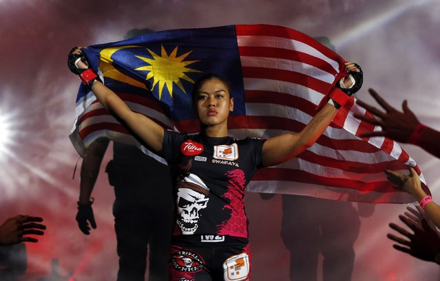 Malaysia's Ann Osman enters the arena carrying the Malaysian flag for her mixed martial arts (MMA) ONE Championship fight against Egypt's Walaa Abbas in Kuala Lumpur, March 13, 2015. (Photo by Olivia Harris/Reuters)