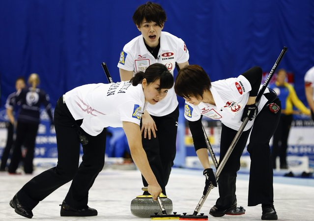 Japan's second Kaho Onodera (C) instructs her teammates Anna Ohmiya (L) and Sayaka Yoshimura while they sweep during their curling round robin game against Scotland at the World Women's Curling Championships in Sapporo March 15, 2015. (Photo by Thomas Peter/Reuters)