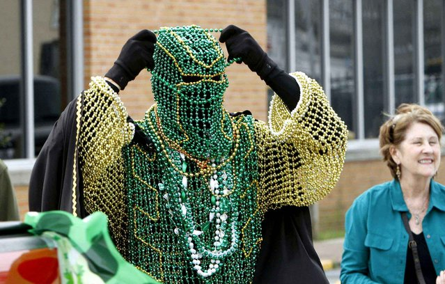 Phillip Davis adds more beads to his costume made of beads at the Hibernia St. Pat's parade in Biloxi, Miss., Saturday, March 14, 2015. (Photo by Tim Isbell/AP Photo/Sun Herald)
