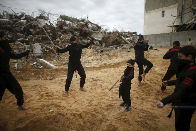 Palestinian youths fight with swords as they demonstrate their ninja-style skills for a photographer in front of the ruins of buildings, that were destroyed in the 2014 war, in the northern Gaza Strip January 29, 2016. (Photo by Mohammed Salem/Reuters)
