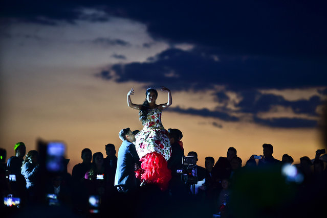 Rubi Ibarra (C) dances during her 15 th birthday celebrations in Villa Guadalupe, San Luis Potosi State, on December 26, 2016. Rubi, a small- town Mexican teen, welcomed thousands of guests for her 15 th birthday party after her parents' video invitation to the milestone event went viral online. (Photo by Ronaldo Schemidt/AFP Photo)