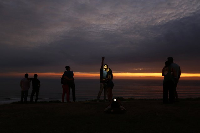 A couple takes a selfie as others observe the sunset at an oceanfront in the neighbourhood of Miraflores in Lima, in this February 9, 2015 file photo. (Photo by Mariana Bazo/Reuters)