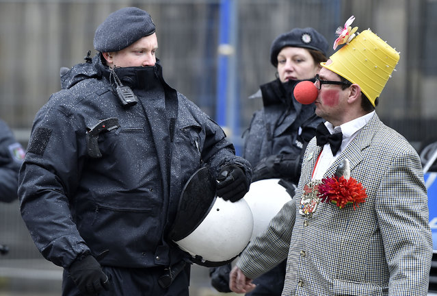 A reveller talks to police during the start of the street carnival in Cologne, Germany, on Thursday, February 4, 2016. After a string of robberies and sexual assaults on New Year's Eve in the city that police say were committed largely by foreigners, German authorities are keen to avoid a repeat of those events during the five-day street party. (Photo by Martin Meissner/AP Photo)