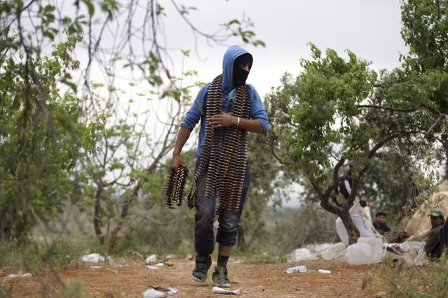 A Free Syrian Army fighter carries ammunition on Nahlaya Front in Idlib, during preparations for an operation to take over Ariha city May 9, 2015. (Photo by Khalil Ashawi/Reuters)