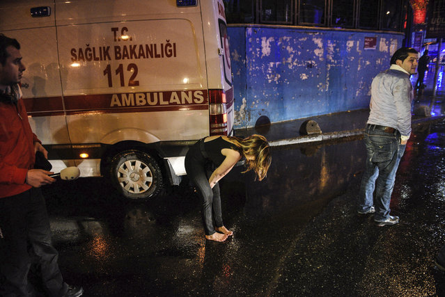 A woman reacts next to an ambulance near the scene of an attack in Istanbul, early Sunday, January 1, 2017. (Photo by AP Photo)