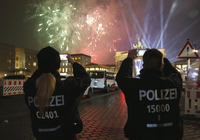German police officers take pictures as fireworks explode next to the Quadriga sculpture atop the Brandenburg gate during New Year celebrations in Berlin, Germany, January 1, 2017. (Photo by Fabrizio Bensch/Reuters)