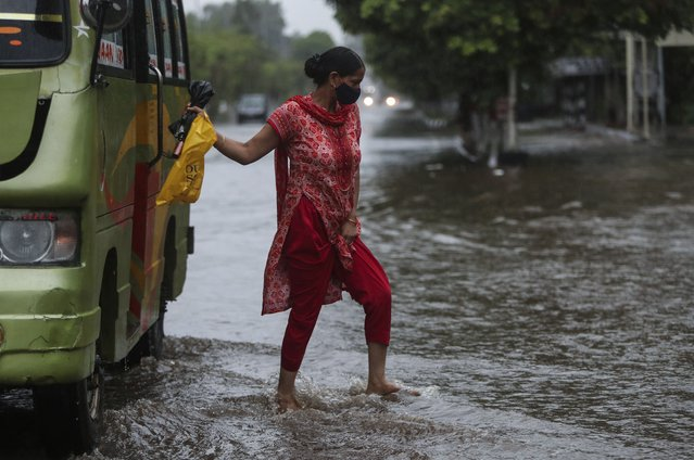 A woman alights from a bus at a flooded street during monsoon rains Jammu, India, Monday, July 12, 2021. (Photo by Channi Anand/AP Photo)