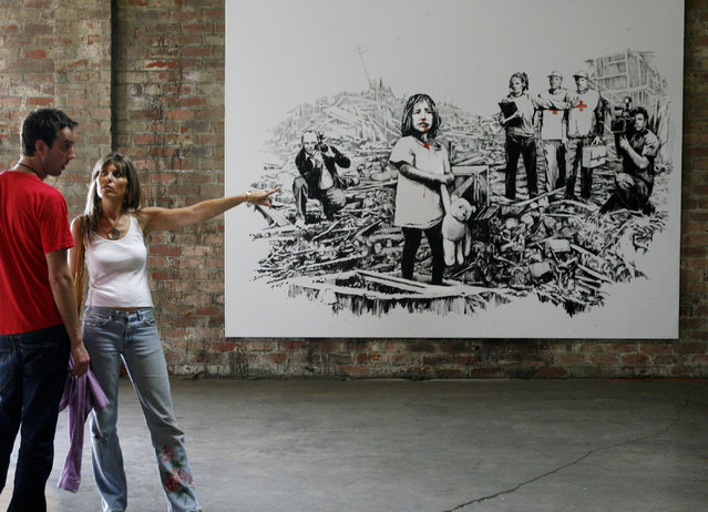 Visitors stand by a painting by Banksy at a 2006 exhibition of his work in Los Angeles. (Photo by Fred Prouser/Reuters)