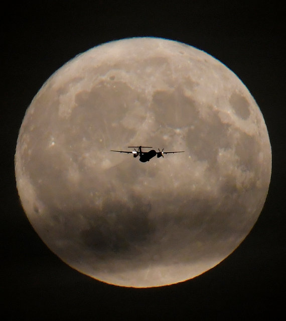 A passenger plane is seen with the full moon behind as it begins its final landing approach to Heathrow Airport in London, Britain, September 24, 2018. (Photo by Toby Melville/Reuters)