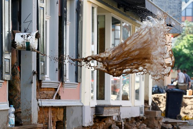 A soldier throws water out of a house, following heavy rainfalls, in Bad Muenstereifel, North Rhine-Westphalia state, Germany, July 21, 2021. (Photo by Thilo Schmuelgen/Reuters)
