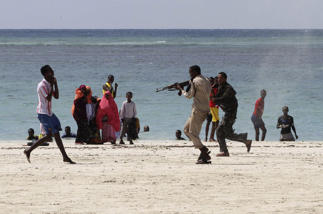 A Somali police officer arrests a suspected rebel member of the al Qaeda-affiliated al Shabaab among beach goers in Mogadishu. Al Shabaab claimed responsibility for today's pre-dawn attack on a Kenyan university campus near the Somali border.  (Photo by Feisal Omar/Reuters)