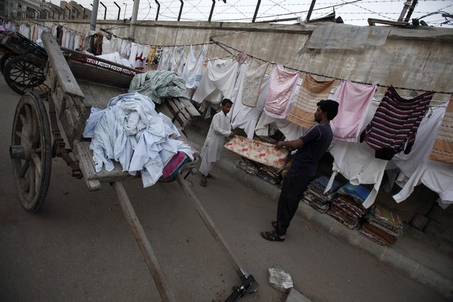 Laundrymen fold a dry sheet of fabric after washing it along a street near the slum area in Karachi February 19, 2015. (Photo by Akhtar Soomro/Reuters)
