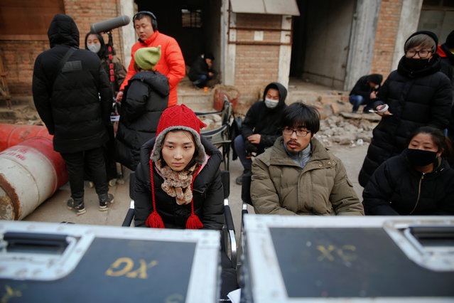 Director Shen Chenyan (2nd R) and executive producer Liu Menghuan (L) watch a scene of the post-apocalyptic movie Zombie Era on the set at an abandoned factory complex in Langfang, Hebei province, China December 16, 2016. (Photo by Damir Sagolj/Reuters)