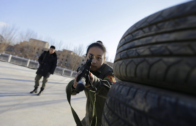 A student aims a replica 95 semi-automatic rifle during training at the Tianjiao Special Guard/Security Consultant training camp on the outskirts of Beijing December 11, 2013. (Photo by Jason Lee/Reuters)