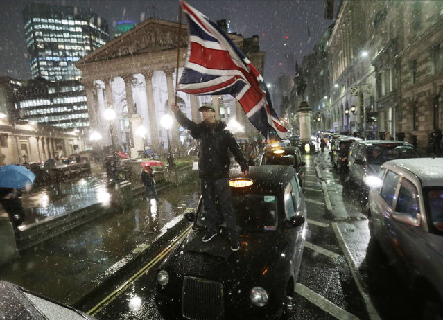 A Taxi drivers' protest gridlocks Bank junction in London's financial district with their black cabs, forcing cyclists and pedestrians to weave around the stopped vehicles during the first UK snows of the winter, on 12th January 2017, in the City of London, England. The drivers are protesting that taxis and other traffic will be banned from here, one of Londons most notorious junctions in a ground-breaking road safety measure to start in April. Only cyclists and buses will be allowed to use Bank junction between the hours of 7am and 7pm after the City of London Corporation after a series of cycling deaths at this location, (Photo by Yui Mok/PA Wire)