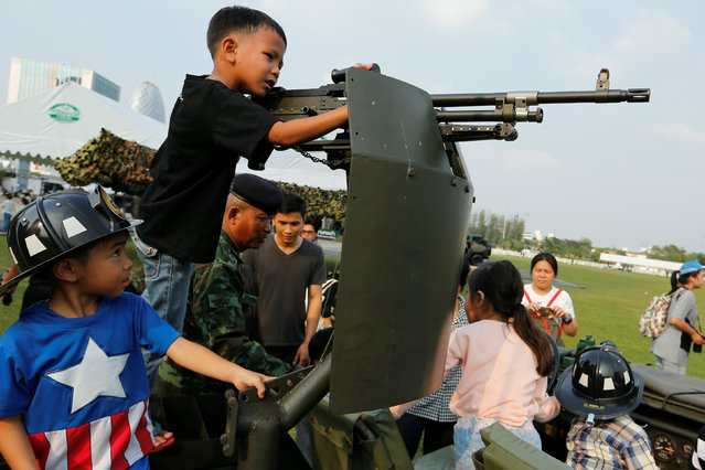 Children play with a weapon on the top of an army vehicle during Children's Day celebration at a military facility in Bangkok, Thailand January 14, 2017. (Photo by Jorge Silva/Reuters)