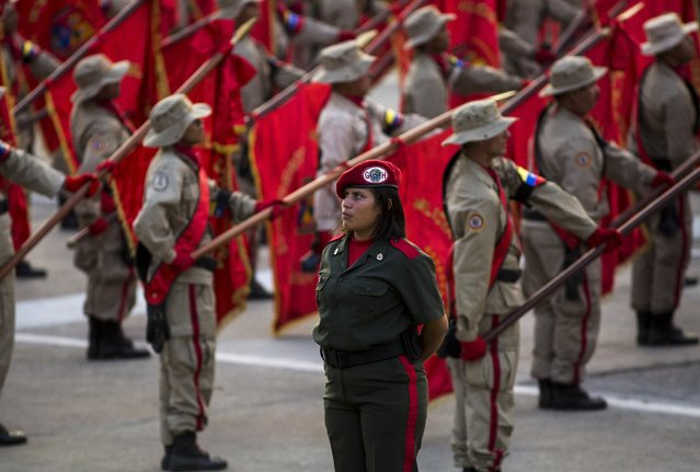 Militia members stand at attention during a ceremony in Caracas April 13, 2015. Supporters of late Venezuelan President Hugo Chavez commemorated 13 years of his return to power after a brief coup that ousted him for two days in 2002. April 13 is now celebrated in the country as the day of the militia. (Photo by Marco Bello/Reuters)