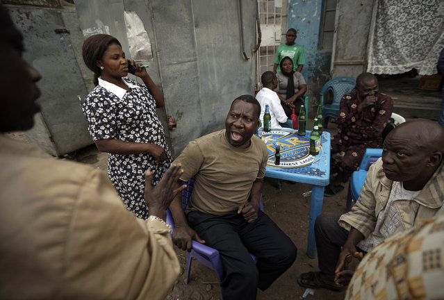 Nigerians engage in heated but friendly arguments about the postponement of the election, over beers at a street-side bar in the predominantly-Christian neighborhood of Sabon Gari in Kano, northern Nigeria Saturday, February 16, 2019. Nigeria's top candidates on Saturday condemned the last-minute decision to delay the presidential election for a week until Feb. 23, blaming each other but appealing to Africa's largest democracy for calm. (Photo by Ben Curtis/AP Photo)