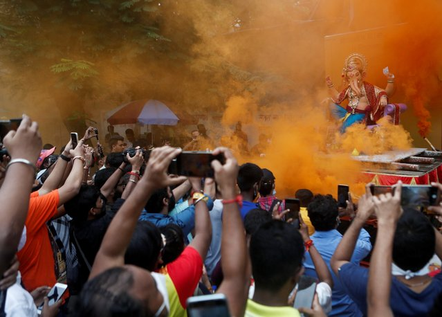 Devotees flock to catch a glimpse of an idol of the Hindu God Ganesh, the deity of prosperity, as it leaves a workshop ahead of the Ganesh Chaturthi festival in Mumbai, India, September 5, 2021. (Photo by Francis Mascarenhas/Reuters)