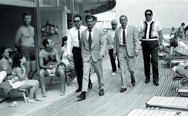 "Frank Sinatra, his stunt double and bodyguards stroll along the Miami boardwalk to the set of ""The Lady in Cement"" in an arresting photograph shot by Terry O'Neill in 1968. (Photo by Terry O'Neill)"