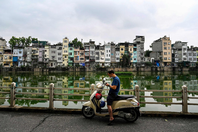 """This photograph taken on June 8, 2021 shows a man checking his mobile phone against the bacdrop of narrow residential houses, known as """"nha ong"""" in Vietnamese or """"tube houses"""", in an urban area of Hanoi. (Photo by Manan Vatsyayana/AFP Photo)"""