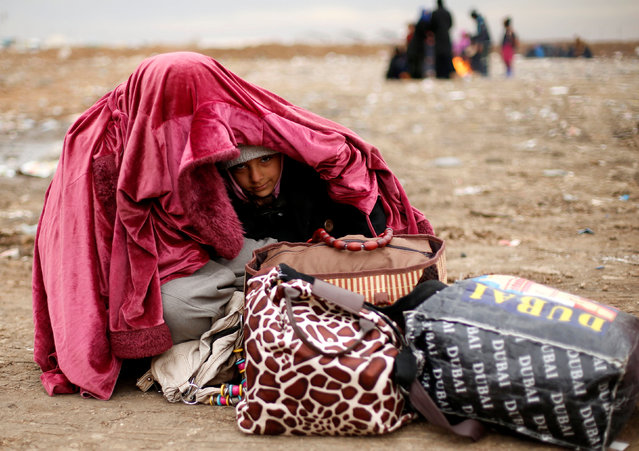 A displaced Iraqi woman covers her daughter during cold weather after fleeing the battle between Iraqi rapid response forces and Islamic State militants near Mosul, Iraq, January 25, 2017. (Photo by Ahmed Jadallah/Reuters)